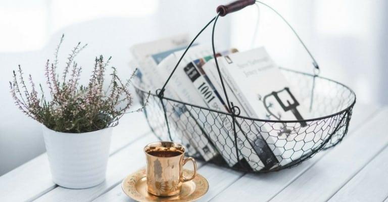 Livres, panier, tasse dorée et plantes