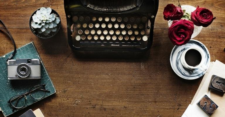 Machine à écrire, appareil photo, roses et café sur table