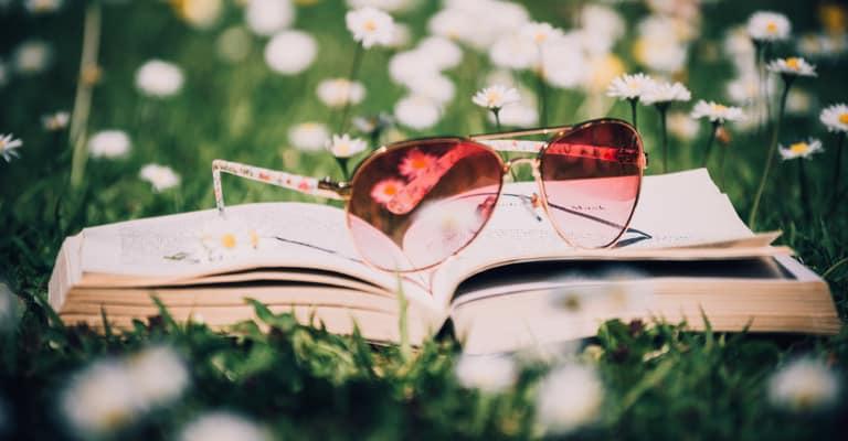 Livre sur herbe avec lunettes roses