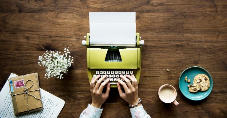 Machine à écrire verte, café, cookie et fleurs